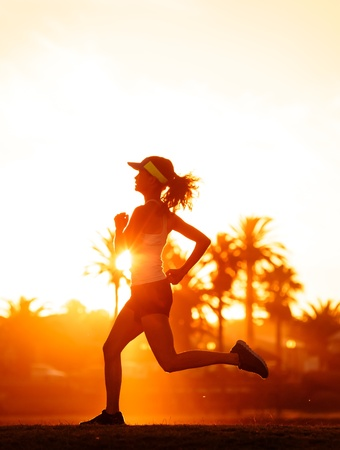 silhouette of a woman athlete running at sunset or sunrise. fitness training of marathon runner. photo