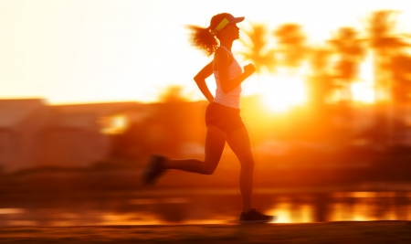 silhouette with motion blur of a woman athlete running at sunset or sunrise. fitness training of marathon runner. photo