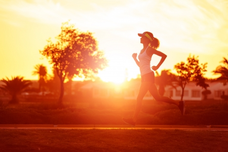 road runner: silhouette of a woman athlete running at sunset or sunrise. fitness training of marathon runner. Stock Photo