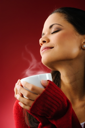 steam mouth: Portrait of a woman drinking a fresh cup of hot coffee with steam isolated on red background Stock Photo