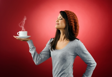 Portrait of a woman drinking a fresh cup of hot coffee with steam isolated on red background photo