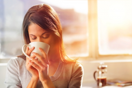 DRINKS: Woman drinking coffee at home with sunrise streaming in through window and creating flare into the lens.  Stock Photo