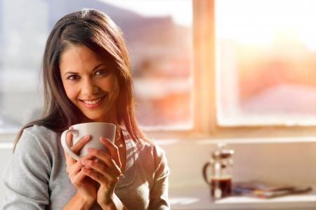 tomando café: Mujer de tomar café en casa con la salida del sol que entraba por la ventana y la creación de destello a la lente.