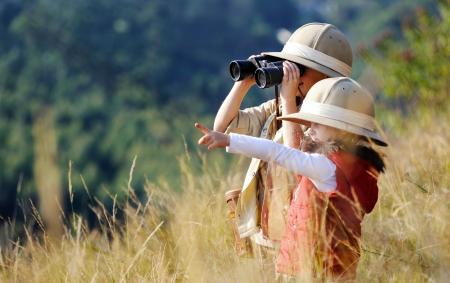 Hermano y hermana niños jugando al aire libre que pretenden ser de safari y divertirse juntos con los prismáticos y sombreros Foto de archivo