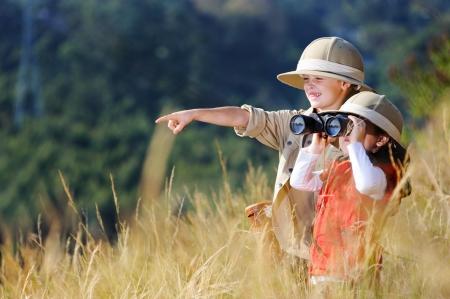Kinderen broer en zus buiten spelen doen alsof ze op safari en plezier samen met een verrekijker en hoeden