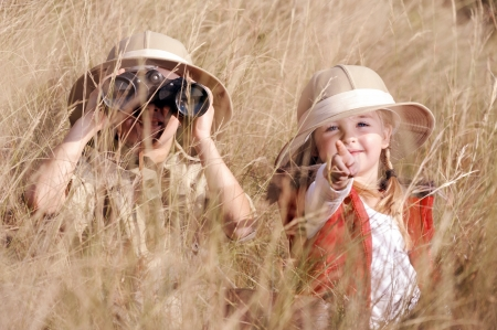 Children brother and sister playing outdoors pretending to be on safari and having fun together with binoculars and hats photo