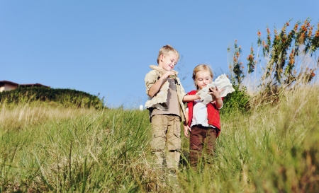 Brother and sister children playing pretend adventure game outdoors having fun in the field photo