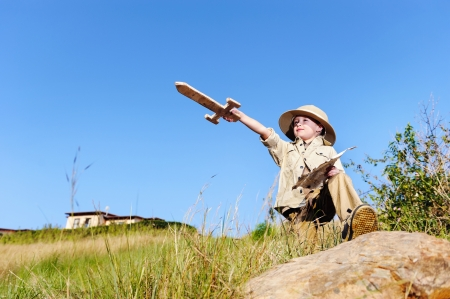 young child playing pretend adventure explorer with wooden sword and treasure map.