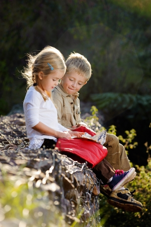 young children playing outdoors, happy brother and sister having fun photo
