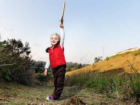 children playing with toys: young girl playing pretend explorer adventure game outdoors. cute young child having fun Stock Photo