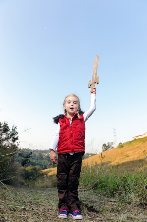 young girl playing pretend explorer adventure game outdoors. cute young child having fun photo