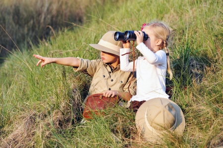 cute children playing pretend safari game together outdoors. happy brother and sister photo