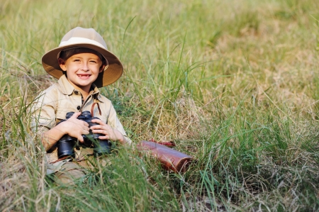 pretend: Young boy child playing pretend explorer adventure safari game outdoors with binoculars and bush hat