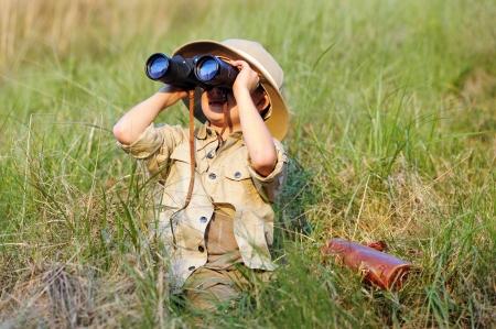 Niño chico joven que juega a fingir explorador de aventura al aire libre juego de safari con binoculares y sombrero arbusto
