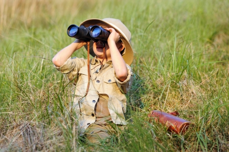 Young boy child playing pretend explorer adventure safari game outdoors with binoculars and bush hat