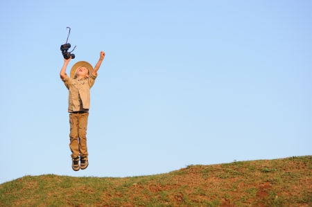 Jumping young child outdoors with binoculars and safari clothing and hat photo