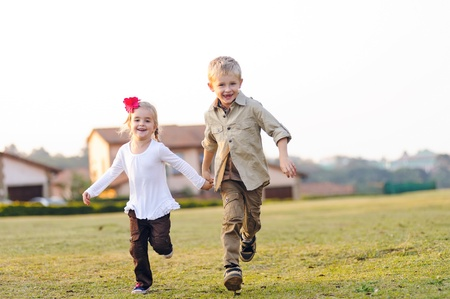 Brother and sister running together outdoors having fun, smiling and laughing photo