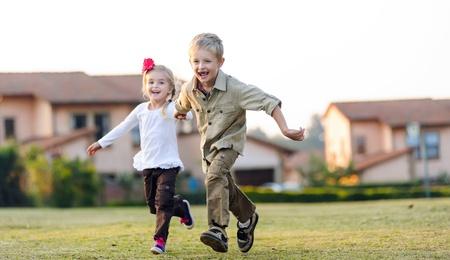 ni�os rubios: El hermano y la hermana corriendo juntos al aire libre divirti�ndose, sonriendo y riendo