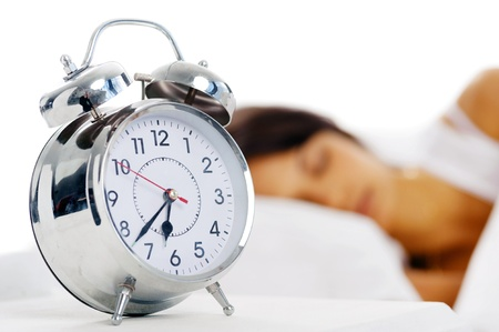 sleeping face: Beautiful sleeping woman resting in bed with alarm clock ready to wake her in the morning. Stock Photo