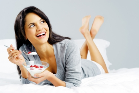 ätande: Frukost kvinna med yoghurt spannmål i sängen äta ett hälsosamt mellanmål med frukt och bekymmersfri leende