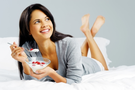Breakfast woman with yoghurt cereal lying in bed eating a healthy snack with fruit and carefree smile photo