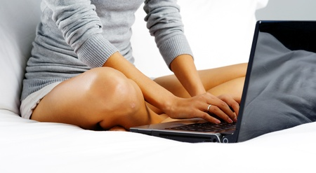 woman typing: Portrait of a woman relaxing at home and using a laptop while lying in bed on grey background Stock Photo