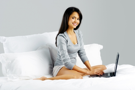 Portrait of a woman relaxing at home and using a laptop while lying in bed on grey background photo