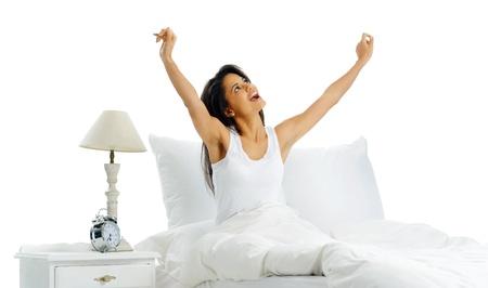 despertarse: Bostezar mujer cansada que despierta en la cama con el despertador y los brazos. aislado sobre fondo blanco