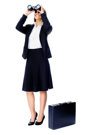 Business vision concept with businesswoman looking through binoculars while wearing a suit and with briefcase isolated on white photo