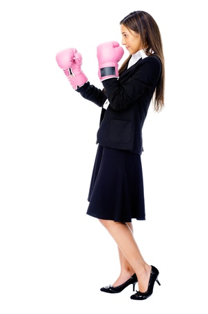 Successful competitive businesswoman is happy and and has boxing gloves while wearing a suit and isolated on white background Stock Photo - 15282832
