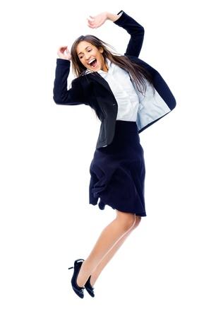 businesswoman suit: Carefree empresaria celebra saltando de alegr�a, de victoria y felicidad mientras sonriente en un traje aisladas sobre fondo blanco Foto de archivo