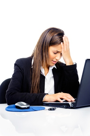 Stressed businesswoman is frustrated and overworked at her desk and computer isolated on white background photo