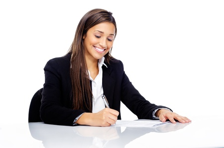 Confident happy businesswoman signing contract at her desk isolated on white background Stock Photo - 15291435