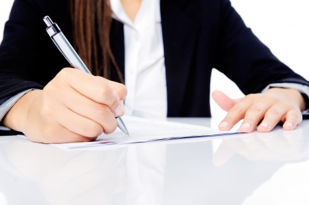 Confident happy businesswoman signing contract at her desk isolated on white background Stock Photo - 15291595