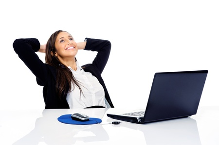 Carefree businesswoman is relaxing at her desk with arms behind her head and daydreaming Stock Photo - 15291428