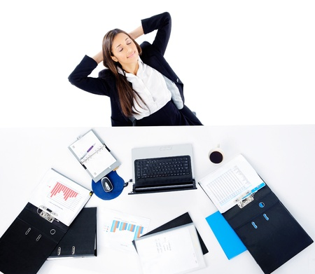 Carefree businesswoman is relaxing at her desk with arms behind her head and daydreaming Stock Photo - 15291542