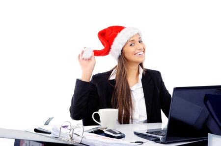 Christmas business woman celebrating the end of work year with a xmas hat at the office photo