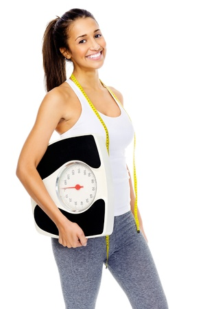 Healthy weightloss woman holding scale and smiling towards camera isolated on white background.