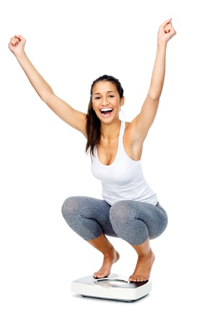 Hispanic woman celebrating and cheering a weightloss goal achievement isolated on white and on a scale photo
