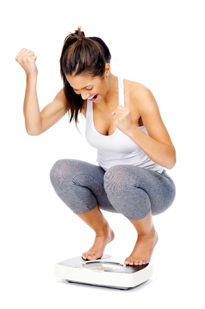 loss: Hispanic woman celebrating and cheering a weightloss goal achievement isolated on white and on a scale