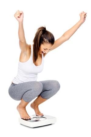 weighing scales: Ispanico, donna celebrare e tifo un risultato obiettivo perdita di peso isolato su bianco e su una scala
