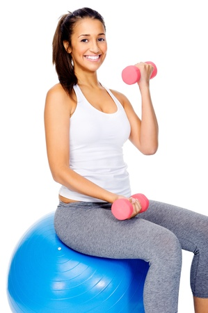 Healthy gym woman working out sitting on swiss ball and using dumbbells isolated on white background photo