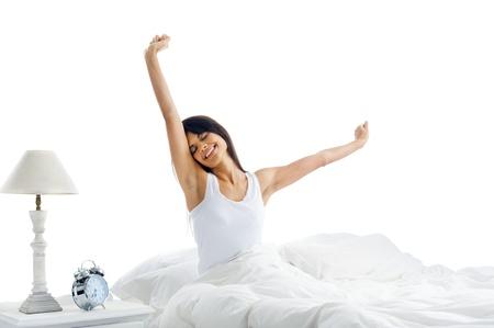 gente durmiendo: Cansado mujer dormida que despierta y que bosteza con un estiramiento mientras est� sentado en la cama aislado sobre fondo blanco Foto de archivo