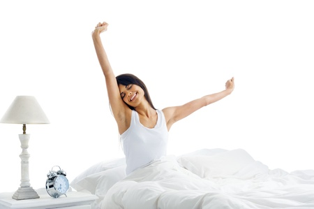 Tired sleepy woman waking up and yawning with a stretch while sitting in bed isolated on white background photo