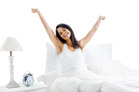 Cansado mujer dormida que despierta y que bosteza con un estiramiento mientras está sentado en la cama aislado sobre fondo blanco Foto de archivo