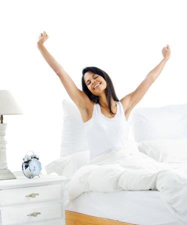 Cansado mujer dormida que despierta y que bosteza con un estiramiento mientras está sentado en la cama aislado sobre fondo blanco