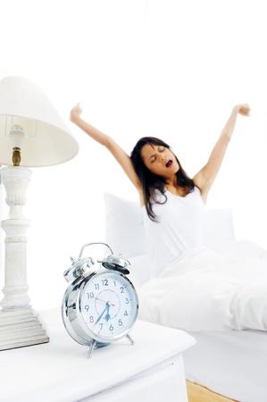 woman clock: Cansado mujer dormida que despierta y que bosteza con un estiramiento mientras est� sentado en la cama aislado sobre fondo blanco Foto de archivo