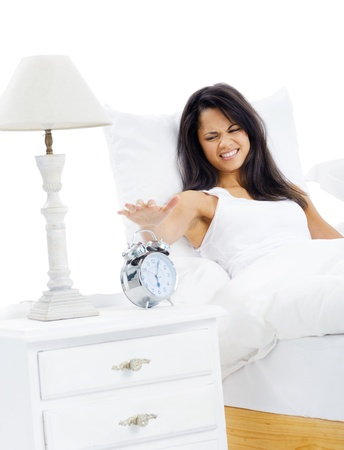 get out: Woman unhappy to wake up early is reluctant to get out of bed isolated on white background
