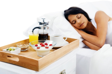 bed and breakfast for attractive young woman sleeping and relaxing with room service isolated on white background photo