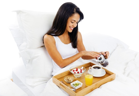 luxury breakfast in bed with coffee and croissant and healthy fruit for attractive young woman photo